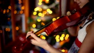 Christmas. Happy girl playing the violin with the Christmas lights behind.