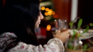 Christmas in Spain. Girl laughing sitting at the table. Christmas lights in background.