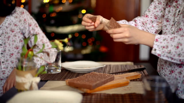 Christmas in Spain. Girl's hands cutting a chocolate nougat and giving a piece to her sister
