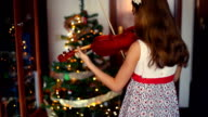 Christmas. little girl playing the violin at home with the Christmas lights behind.