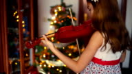 Christmas. little girl playing the violin with the Christmas lights behind.