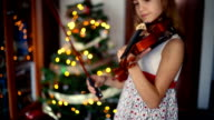 Christmas. Little girl preparing the violin to start playing.