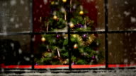 Christmas Tree at window with snow falling - DOLLY