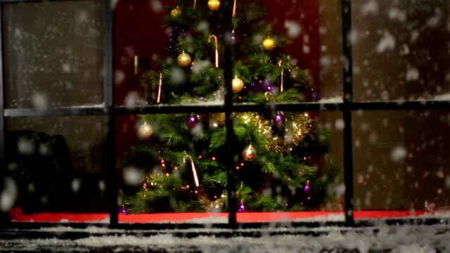 Weihnachtsbaum mit Schnee fallen am Fenster