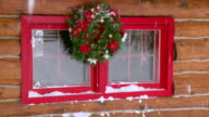 MS Christmas wreath on log home window during winter / Tweed, Ontario, Canada