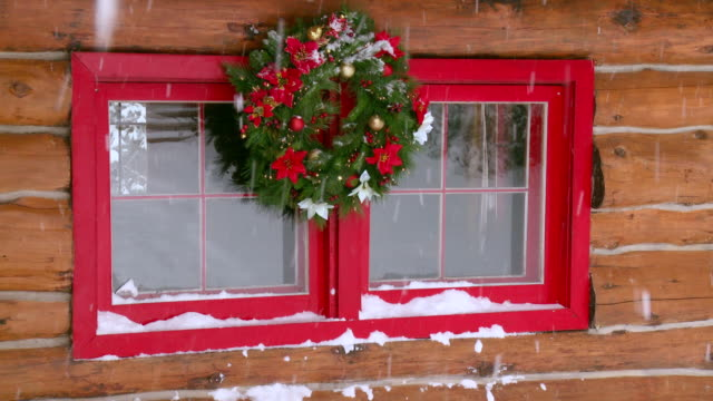 MS Christmas wreath on log home window during winter / Tweed, Ontario, Canada