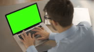 Chroma key laptop, office worker typing at desk.