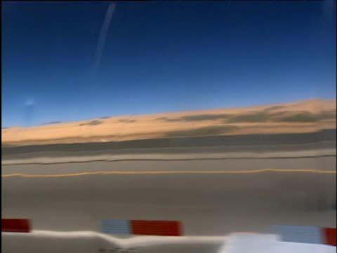Chrome oil tanker drives along straight open desert road