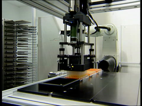 Chromosone deciphered ITN GVs Electronic testing machine placing samples of genetic material in test tubes GV Robotic arm picking up genetic sample...