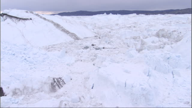Chunks of ice form a rough surface on a glacier. Available in HD.