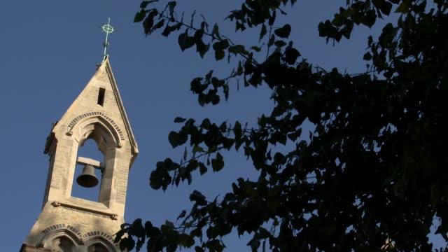 A church bell tower overlooks a tree.