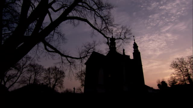 A church looms behind silhouetted trees. Available in HD.