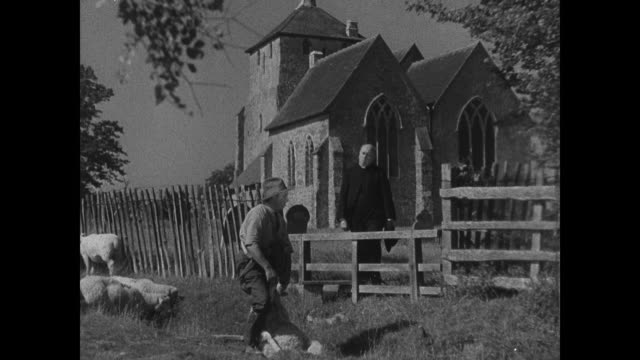 Church of England Parish priest minister leaving church walking on road being ignored by people REPRISING CONVERSATION Farmer sheering sheep while...