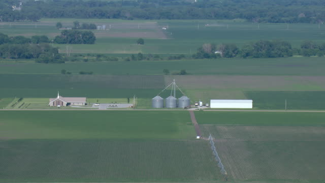 Church out in the country with grain silos next to it
