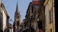 MS ZO WS Church tower and narrow street seen through archway / Sauternes, Aquitaine, France