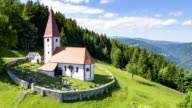 Church with cemetery in the mountains - aerial view - source file cinema dng