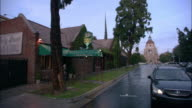HA Church with large steeple at the end of street, pedestrians walking and car driving past corner bar and grill a rainy day / Pasadena, California, United States