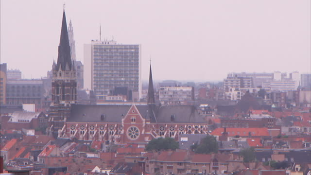 A church with ornate spires nestles in buildings in Antwerp.