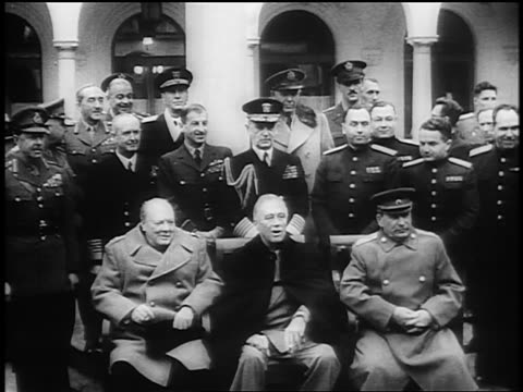 Churchill Roosevelt Stalin sitting together at Yalta Conference / men in uniform in background