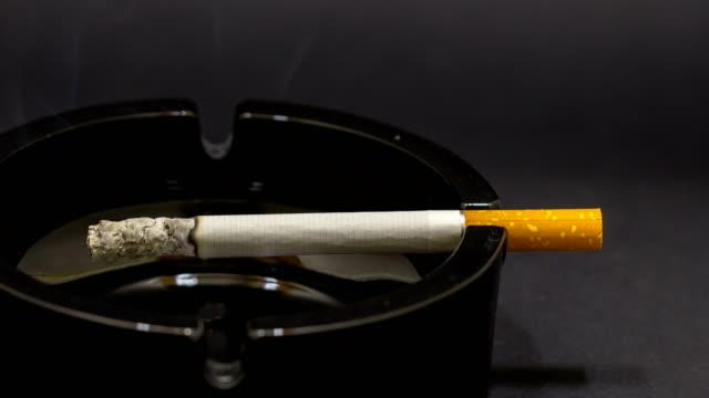 Cigarette burning in the ashtray