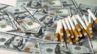Cigarettes Falling on Dollar Notes, Slow Motion 4K