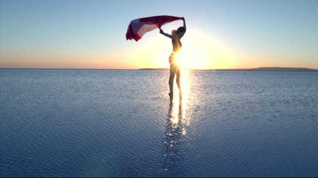 Cinemagraph of beautiful dancer holding a Canadian National Flag on the lake. A windy day.