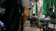 Cinemagraph of Senior woman sitting in market with young man.