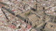 circling aerial view of Seville cathedral with La Giralda belfry and the Archivos de las Indias The General Archive of the Indies; the square building to the right of the cathedral)