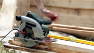Circular saw on a wooden plank. The builder takes the circular saw.