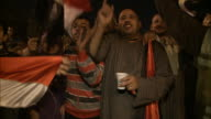 Citizens celebrating in the streets holding a banner with Arabic text families smiling and waving flags showing off their babies carrying happy...