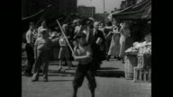 City children playing stickball on street buildings BG MS Boy batting w/ stick people in market watching BG MS Boys shooting craps WS Children...