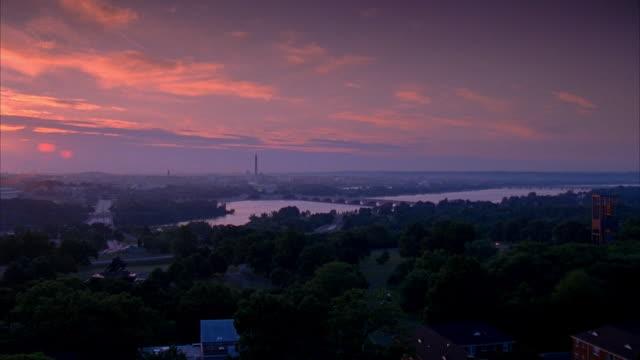 PAN City Potomac River Theodore Roosevelt Memorial Bridge Virginia trees buildings below FG yellow pink purple sky