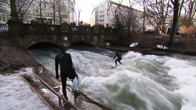 City slickers in Munich are braving the deep freeze to surf on one of the German city's rivers River surfing in Munich started about 30 years ago but...