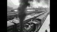 City street HA WS Railroad yard w/ coal engine locomotive train black smoke moving under People running along side full moving railroad car LA Train...