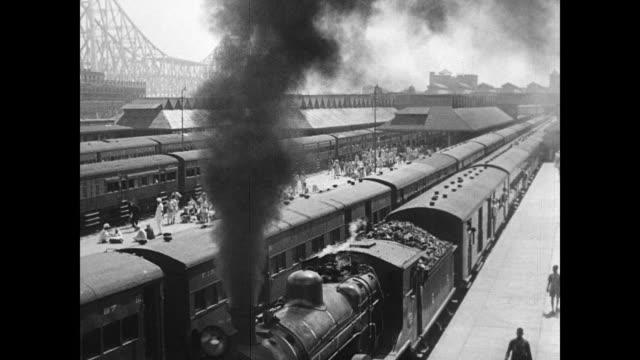 City street HA WS Railroad yard w/ coal engine locomotive train black smoke moving under People running along side full moving railroad car LA Train...