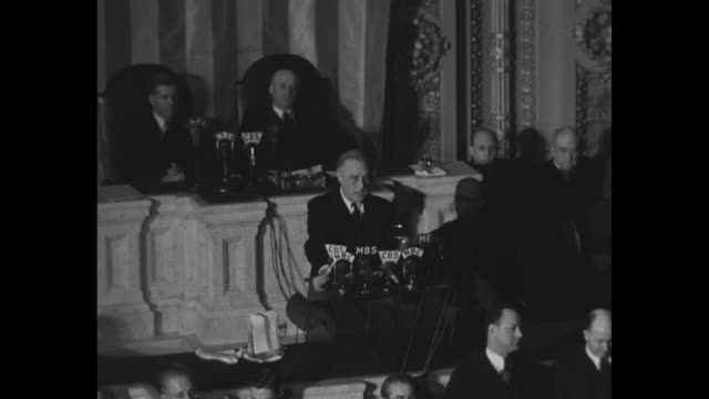 City street with people crowded on sidewalk listening to President Franklin Roosevelt's speech to a joint session of Congress / MS men by car window...