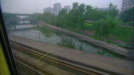 WS POV City streets and buildings as seen from moving passenger train, Jinan, Shandong, China
