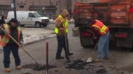 WGN City Workers Filling In Potholes on January 11 2014 in Chicago Illinois