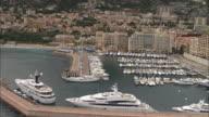 AERIAL WS PAN Cityscape and marina to sunlight reflecting on sea / Monaco