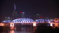 Cityscape PAN to WS Lighted Shelby Street Bridge over Cumberland River pedestrian truss bridge w/ city BG