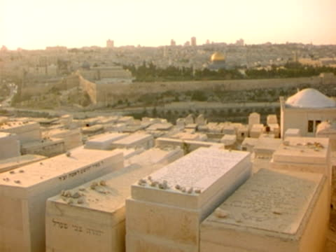 WS, cityscape with tomb stones in foreground at sunset, Jerusalem, Israel
