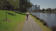 4K Cityscapes, Landscapes & Establishers: aerial view of Yarra River, man cycling and Melbourne city