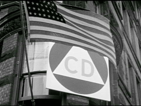 Civil Defense triangle on building near American flag Small group of city officials meeting at desk Threats Nuclear biological chemical enemy...