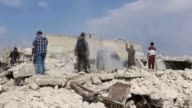 Civilians and civil defense team members work on the rubble of a destroyed building after warcrafts belonging to Syrian army carried out air strikes...