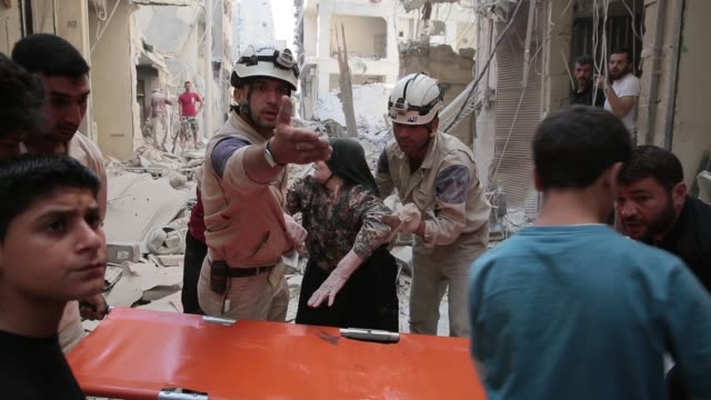 Civilians and members of the Hanano Civil Defense team a group of volunteer first responders help carry away an injured woman from the site of a...