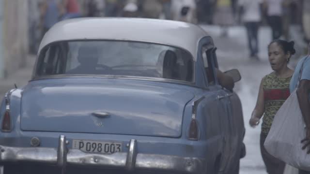 Classic car weaves through pedestrians in Havana