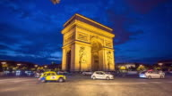 Classic cars passing at the front of Arc de Triomphe in Paris at night.