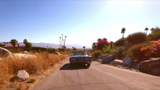 CS classic open convertible car turns a corner then drives up a hill as camera swoops up revealing Coachella Valley desert landscape in far distance
