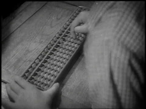 1939 MONTAGE classroom with teacher writing on chalkboard, student using an abacus and a student going to front of class to answer a question / Japan