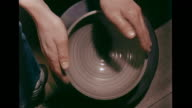 Clay pot turning counterclockwise on potter's wheel raw clay swirling outward pattern VS Male potter using foot to turn wheel below connected to...